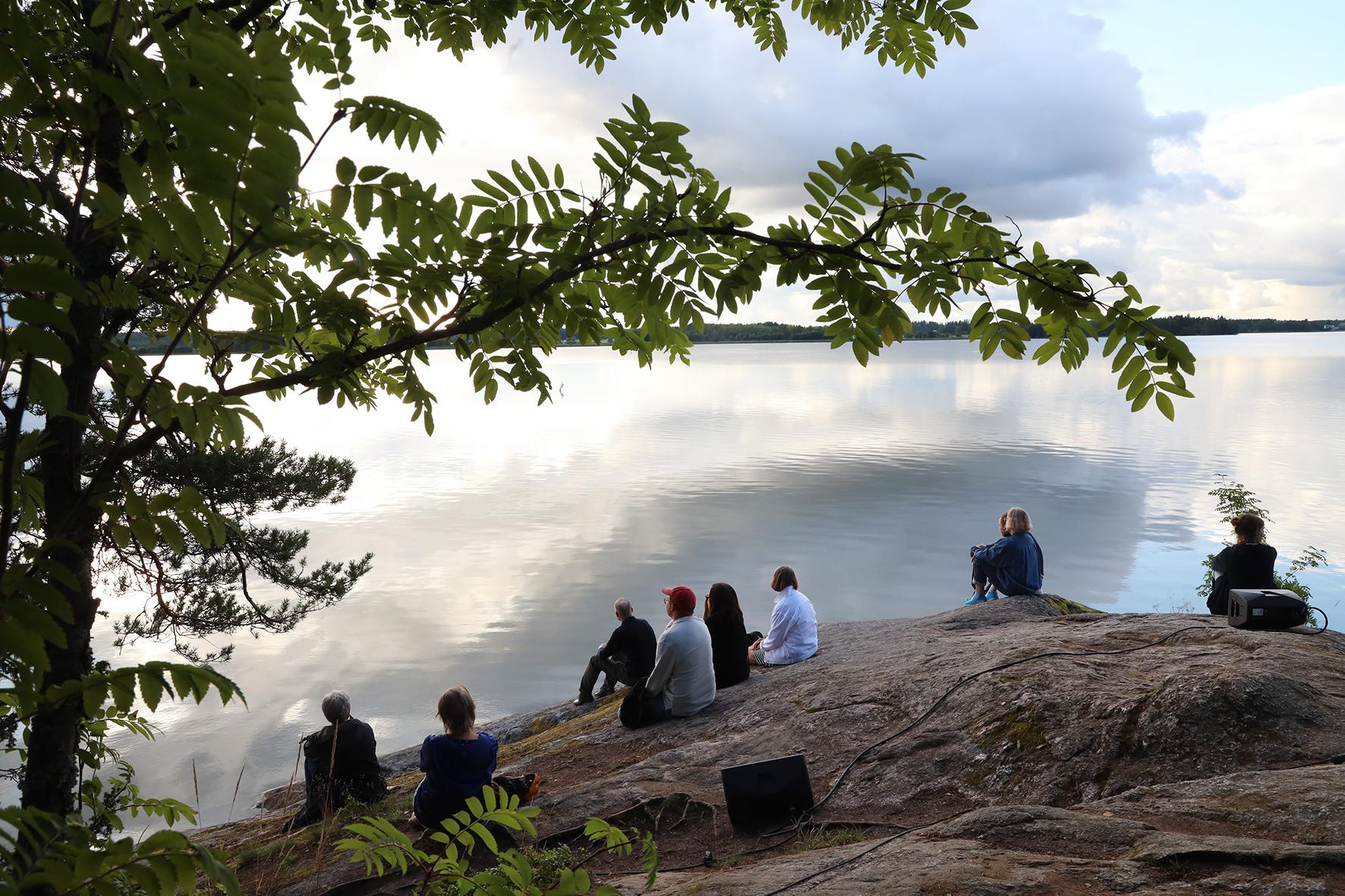 Joukko ihmisiä istuu Tuusulanjärven kallioisella rannalla ja katselee järvelle päin