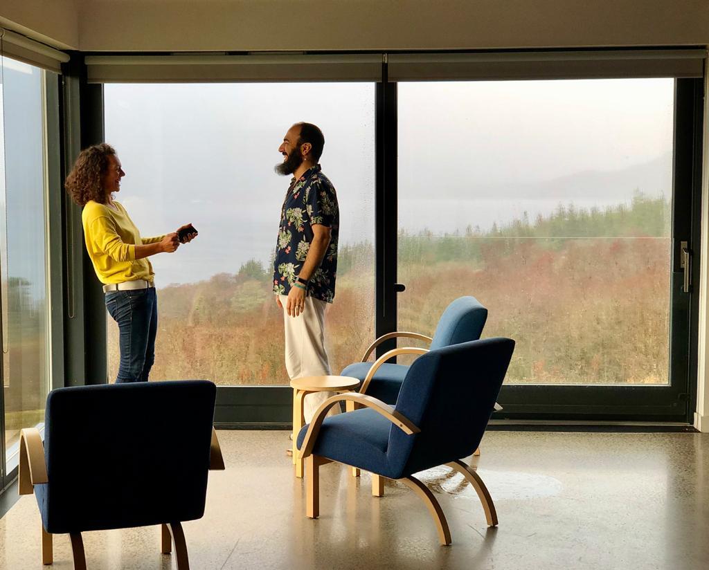 Kuvassa keltapuseroinen nainen ja hawajipaitainen mies keskustelevat eloisasti huoneessa, josta avautuu näköala skotlantilaisille nummille