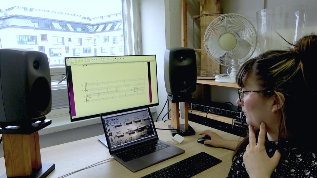 Tytti Arola katselee tietokoneen näyttöä, jolla näkyy nuottiviivastoa ja äänikarttoja.
